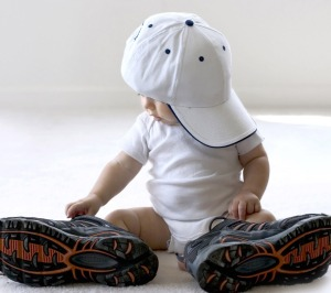 Baby wearing big hat and big shoes